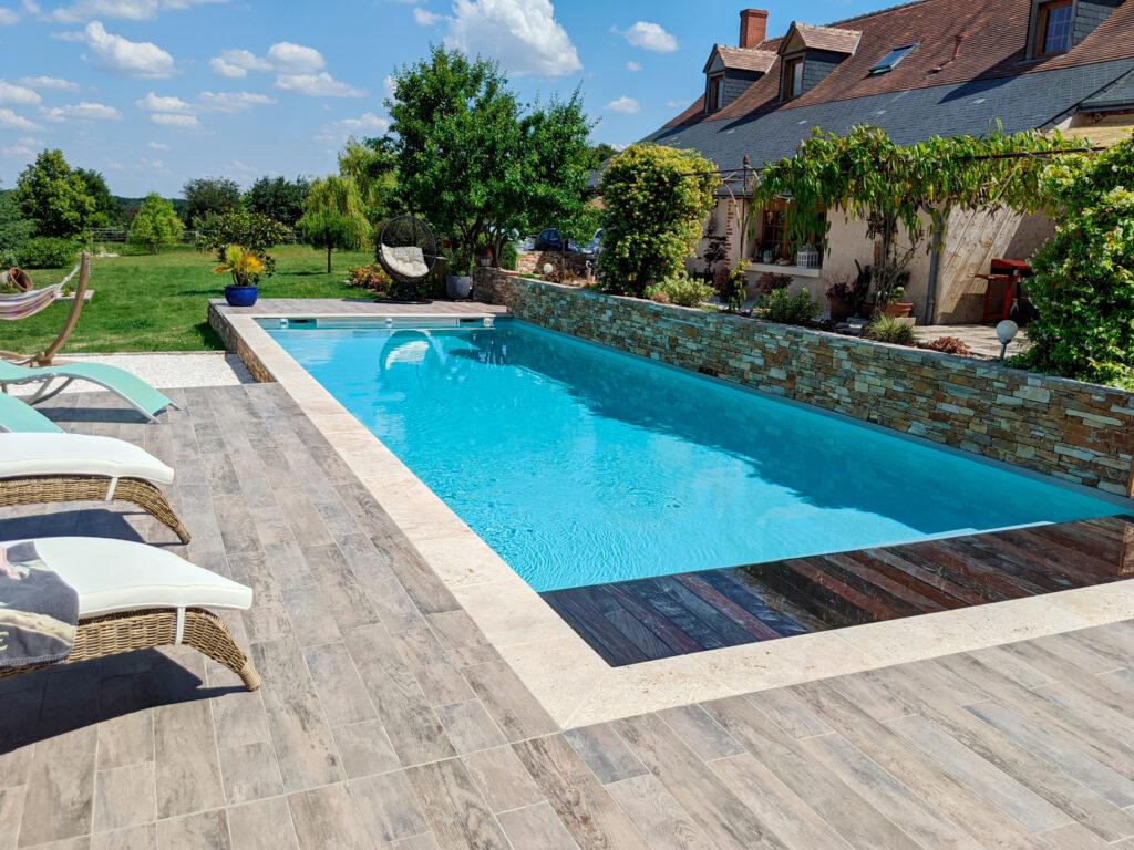 Hydro Loisirs - Construction d'une piscine 10 x 5 m avec liner gris et volet immergé avec caillebotis